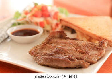 Pork steak with french fries on a  table