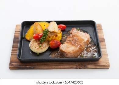 Pork steak with fried potatoes ,pepper and onions on a cast-iron brazier on white background