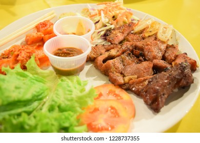 Pork steak, kimchi mixed. background yellow color.