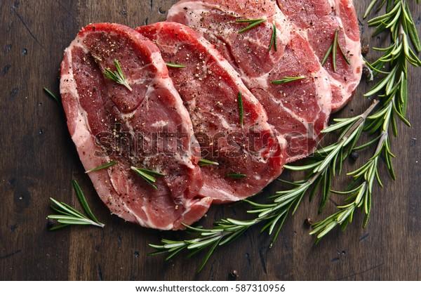 Schweinehefleisch mit Rosmarin und Pfeffer auf einem alten Holztisch