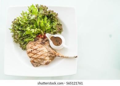 pork steak with salad on white plate