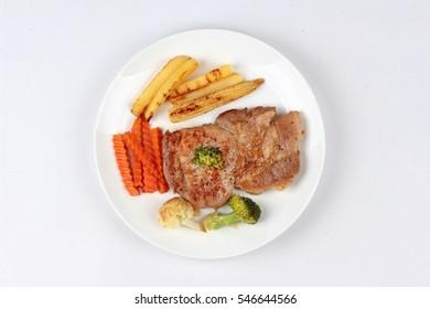 Pork steak with sliced carrot ,potato ,corn ,broccoli and cauliflower.