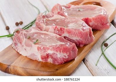 pork steaks on a wooden board. Selective focus