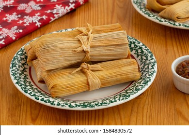 Pork Tamales on a white and green plate on a pine table with a red napkin and salsa