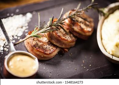 Schweinefleisch-Tenderloin mit Kartoffelbrei, Speck und Senf-Sauce, mit einem Zweig Räucherrosemarie bedeckt