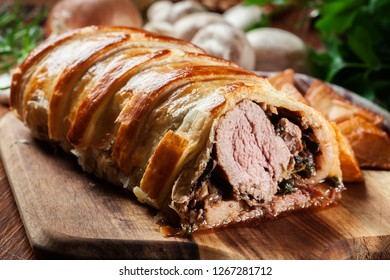 Pork tenderloin in wellington style with mushrooms in puff pastry