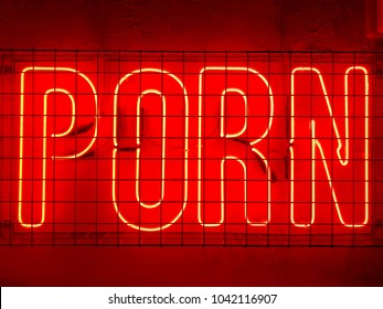 Porn red neon sign fixed to a wall behind metal cage