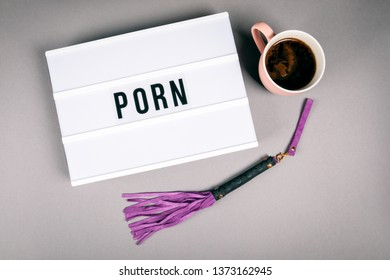 Porn. Text in light box. Pink coffee mug on gray background