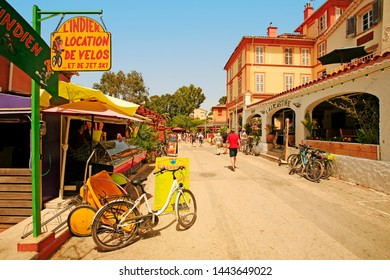 Porquerolles, French Riviera / France - 07-02-2017: street of the village of Porquerolles with signs, houses, bikes for rent and tourists