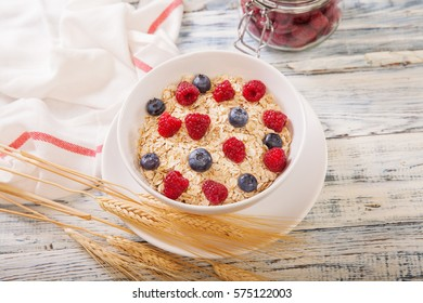Porridge being garnished with fresh berries blueberries and raspberry