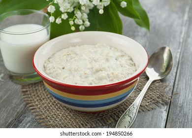 Porridge, milk and lily of the valley on the table