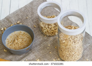 Porridge with nutlets in bank.Bowl of oats porridge isolated on a white background. Healthy breakfast.