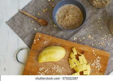 Porridge with nutlets in bank.Bowl of oats porridge isolated on a white background. Healthy breakfast. Porridge with yellow mango