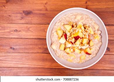 Porridge with peach, apple, banana and walnut on a wooden table