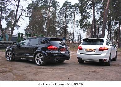 Porsche Cayenne and Porsche Cayenne Turbo TechArt in the forest. Back view. Kyiv, Ukraine, April 4, 2015. Editorial photo.