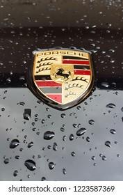 Porsche logo on black car with rain drop. Bangkok, Thailand. - Oct 20, 2018.
