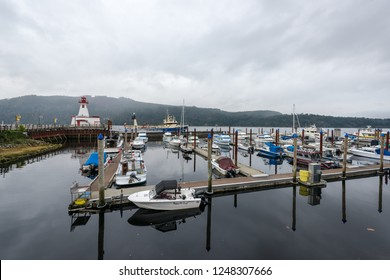 Port Alberni, British Columbia/Canada - September 19, 2018: Boats docked in the calm marina on a cloudy day with a museum in the old lighthouse in the background known as the Maritime Discovery Centre