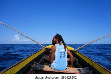 PORT ANTONIO, JAMAICA - DECEMBER 31, 2013: Unidentified Rasta fisherman in a traditional Jamaican wooden fishing boat in Port Antonio, Jamaica on New Year's Eve 2013.