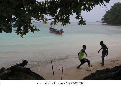 Port Antonio, Portland, Jamaica - 17th June 2017 : Two kids are playing football under heavy rain at the famous Winnifred Beach near Port Antonio, Jamaica