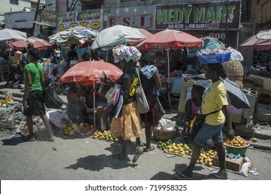 Port Au Prince, Haiti - Circa August 2015: People balance on their heads some goods at the local market in Port Au Prince