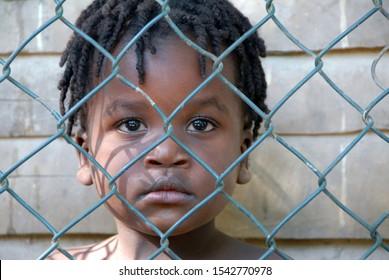 Port au Prince, Haiti / Santo Domingo island - 09/23/2014: Portrait of sad Haitian child behind a wire fence. Sadness Poverty Symbol. No to racism and poverty