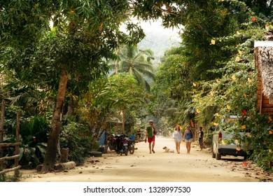 Port Barton, Palawan, Philippines - February 3, 2019: People walk along street with dirt road in traditional Philippine village