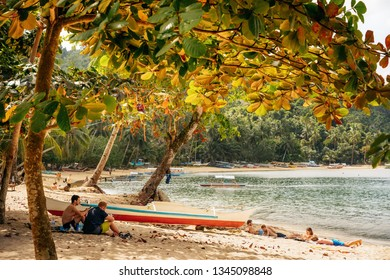 Port Barton, Palawan, Philippines - February 3, 2019: People relax on tropical beach under the lush crown of trees