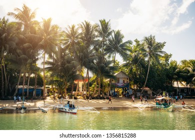 Port Barton, Palawan, Philippines - February 4, 2019: People on tropical beach with trees. Traditional boats in water