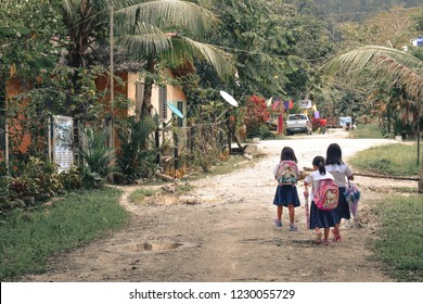 PORT BARTON, THE PHILIPPINES - 16 NOVEMBER 2017 - Little girls walking to primary school on a muddy road in the morning in tropical conditions of Port Barton Palawan the Phillipines