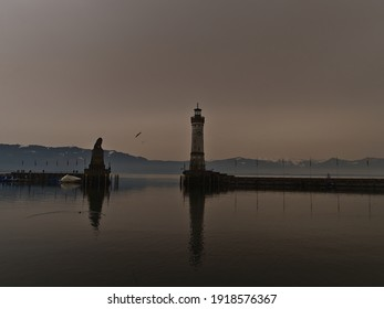 Port basin of Lindau, Lake Constance, Germany with lighthouse and lion sculpture on winter day. Orange colored sky due to rare weather phenomenon, when desert sand particles of Sahara are in the air.