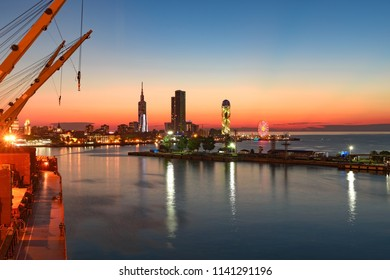 Port of Batumi, Georgian resort city and port at Black Sea – panoramic view of city centre from cargo ship in port in colourful summer sunset light