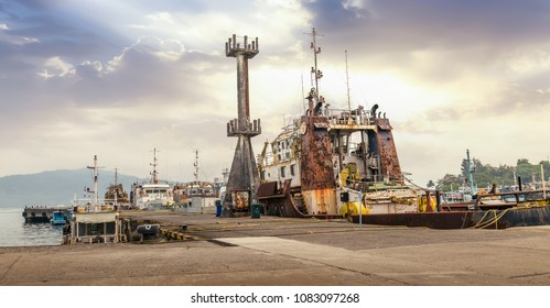 Port Blair harbor Andaman India with view of shipping vessels cranes and a vintage rusty ship at the dockyard.