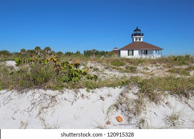 The Port Boca Grande Lighthouse on Gasparilla Island, Florida viewed from the sand dunes with sea oats (Uniola paniculata) and sea grape (Coccoloba uvifera) in the foreground and a clear blue sky