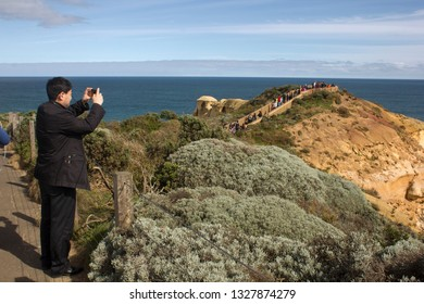Port Campbell, Victoria/Australia- September 3 2016: Asian tourist taking a photograph at The Twelve Apostles in Port Campbell National Park in Victoria, Australia.