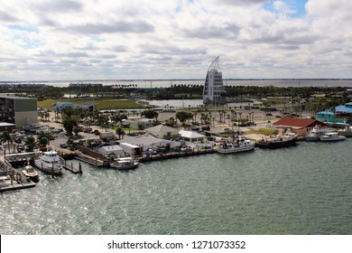 Port Canaveral FL/USA: December 10, 2018 – View of Exploration Tower, yachts and fuel dock at water's edge in Port Canaveral at dusk on a cloudy day. Open water is visible in distance.