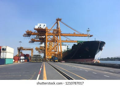 Port with cargo vessel during cargo operation in the day time as for industry, shipping logistics background.