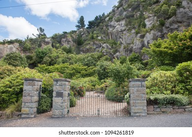 Port Chalmers, Dunedin, New Zealand-December 11,2016: Open public garden with pillars at entr?ance to the lush greenery and rugged mountain landscape in Dunedin, New Zealand