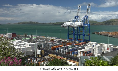 PORT CHALMERS, NZ - DEC. 2015: Wide shot Port Chalmers activity, shipping containers, loading crane, gorgeous sky.  New Zealand South Island's busiest terminal.