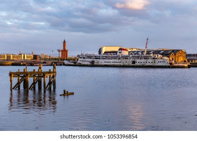 Port Clarence, County Durham, England, UK, May 13, 2016: The shore of the River Tees, looking towards Middlesbrough with the old clock tower and a shipwreck