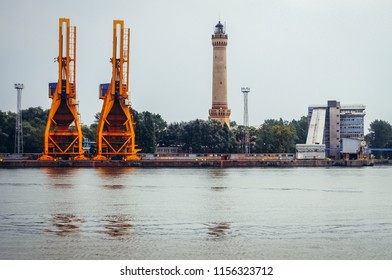 Port cranes and lighthouse in Swinoujscie city on the Baltic Sea coast in West Pomerania region of Poland