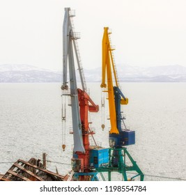 Port cranes on commercial seaport Petropavlovsk-Kamchatsky City on shore of Avacha Bay in Pacific Ocean.