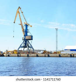 Port cranes over the surface of water in the port of Riga on a clear day, Latvia