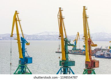 Port cranes and ships on commercial seaport Petropavlovsk-Kamchatsky City on shore of Avacha Bay in Pacific Ocean.
