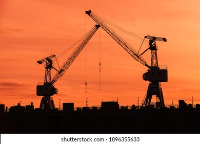 Port cranes silhouettes over red sunset sky, industrial transportation photo