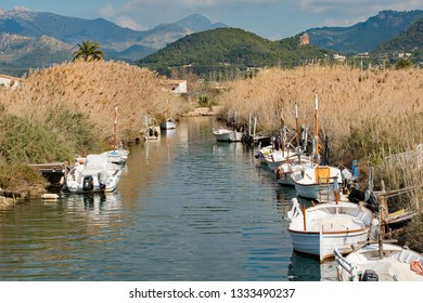 Port d'Andratx, Mallorca. 20th February 2019. Small white sailing boats moored along the reed lined river bank, with the Tramuntana Mountains in the background at Port d'Andratx, Mallorca, Spain.