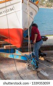 Port d'Andratx, Mallorca. 20th February 2019. Boat owner painting the underside of her small fishing boat, which sits out of the water on wooden supports in the bay at Port d'Andratx, Mallorca, Spain.