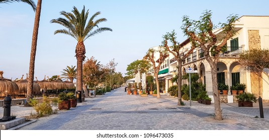 PORT DE POLLENCA, SPAIN - MAY 21 2018: The hotels and shops facing the bay in the early morning. Port de Pollensa is a small town in northern Majorca, Spain, situated on the Bay of Pollensa.