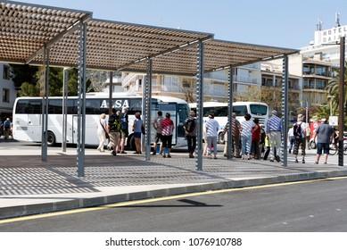 Port de Pollensa, Majorca, Spain. 2018. Tourists waiting for tour bus at the town bus station