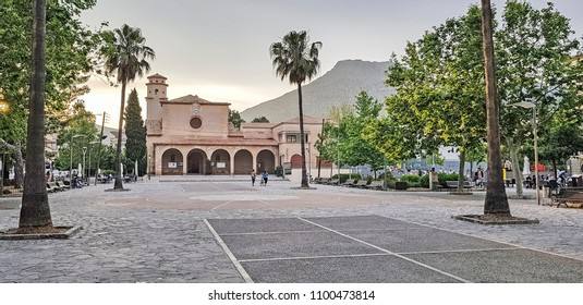 PORT DE POLLENSA, MALLORCA - MAY 20 2018: An urban square with church behind. Port de Pollensa is a small town in northern Majorca, Spain, situated on the Bay of Pollensa.