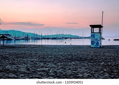 PORT DE POLLENSA, MALLORCA - MAY 20 2018: The The beach with life guard post in the early morning. Port de Pollensa is a small town in northern Majorca, Spain, situated on the Bay of Pollensa.